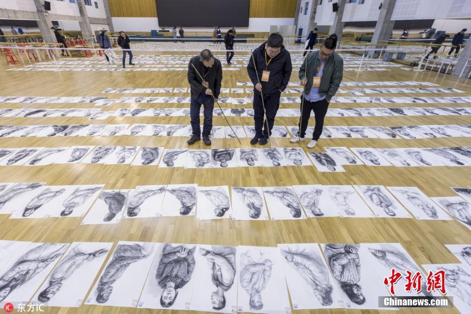 <p>2018年3月19日,位于浙江杭州的中国美术学院进行2018年本科招生评卷工作,考生作品被铺满两座体育馆。美院的老师们手持竹竿来回踱步,神情专注地对考生试卷一一归档评分。 黎耀辉 摄 图片来源:东方IC 版权作品 请勿转载</p>