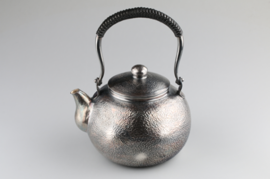一把银壶带来的改变   1994年寸银匠工厂成立初,11名匠人,产生出了一批批质地精美、工艺繁复且精湛的银器,而寸彦同由于其錾刻工艺出神入化,受邀参与寸发标第一套九龙壶的研发制作,已然成为新华村錾刻大师级人物。   随着社会生活的变迁和发展,市场对纯手工艺品的需要与日俱增,寸银匠打造出的银器饰品器型优雅,雕工精湛,前来新华村寻找寸银匠的客商络绎不绝。颇为偶然,一次,一位广东客商递给寸彦同一把精致的银壶,问可制否?寸彦同仔细观察该壶,壶身细雅,出水顺畅,手感极好,经询问,该壶产自日本。   200